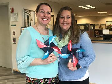 women wearing blue holding pinwheel