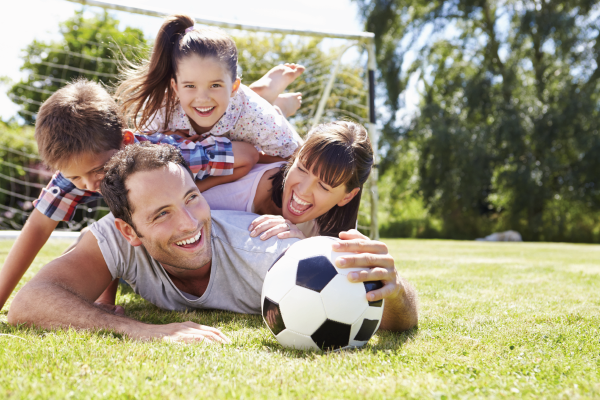 family staying physically well by playing soccer