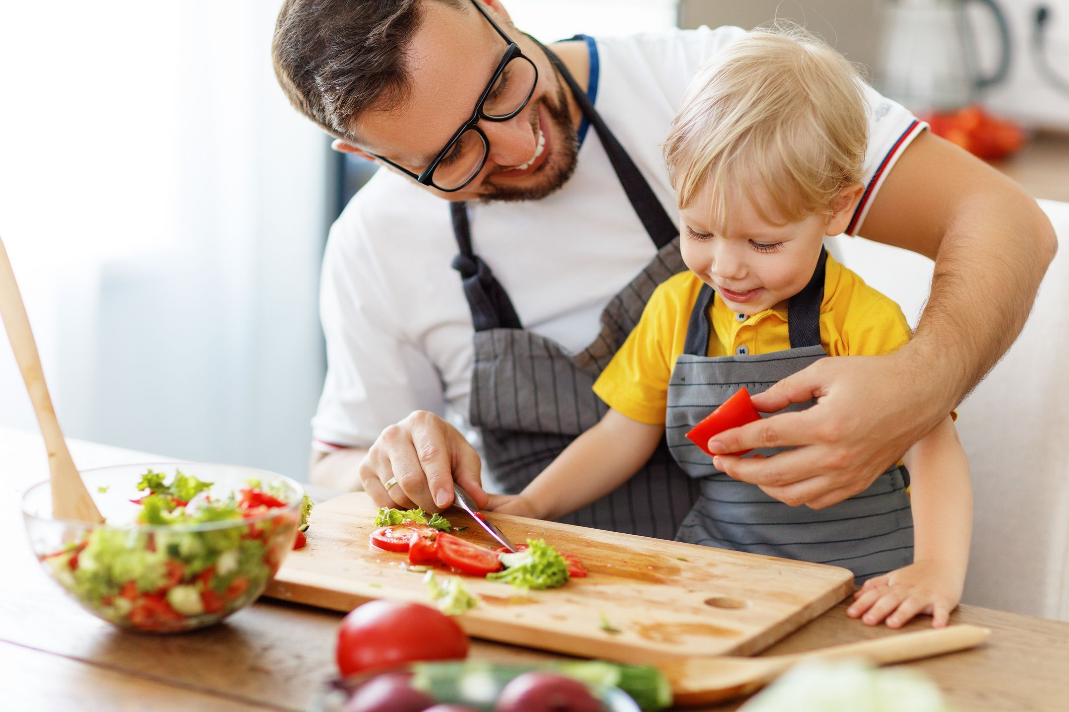 father and son making family meal together