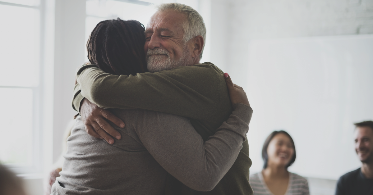 two adults hugging in mental health support group