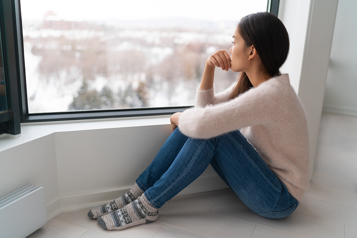 woman with seasonal affective disorder looking out of a window