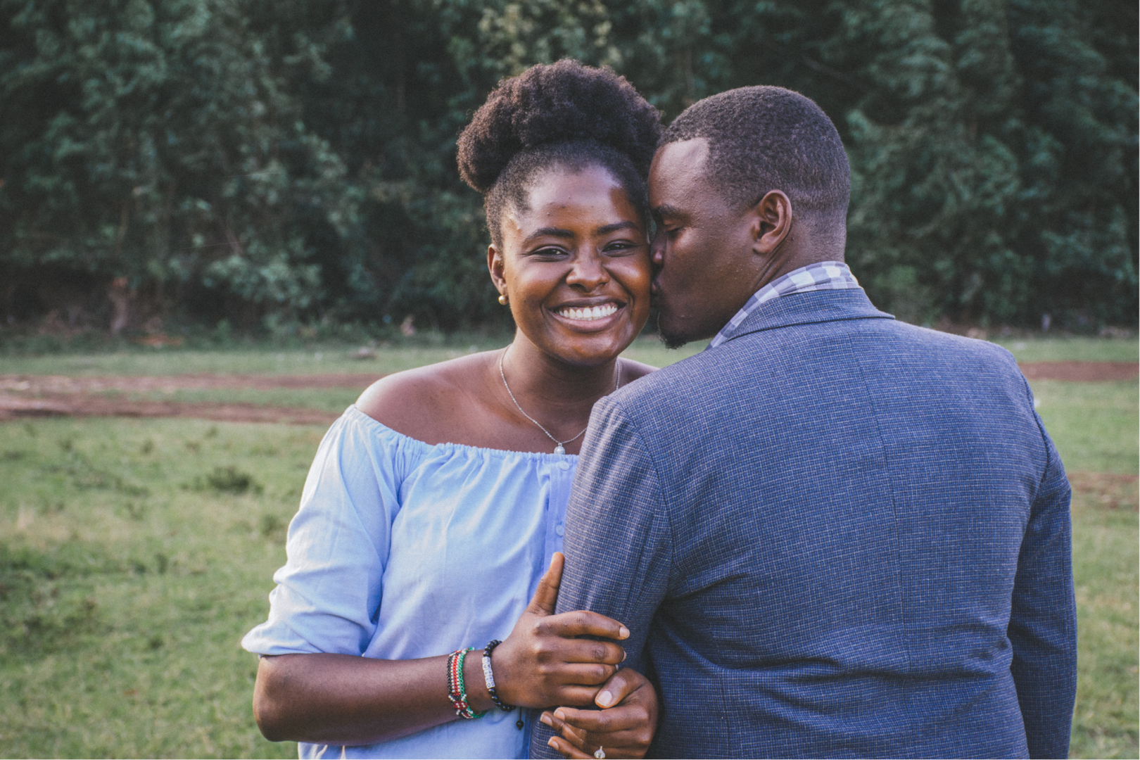 man kissing left cheek of smiling happy woman