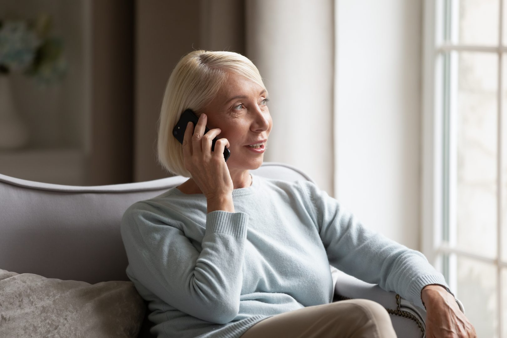 older woman staying social during social distancing by talking on phone
