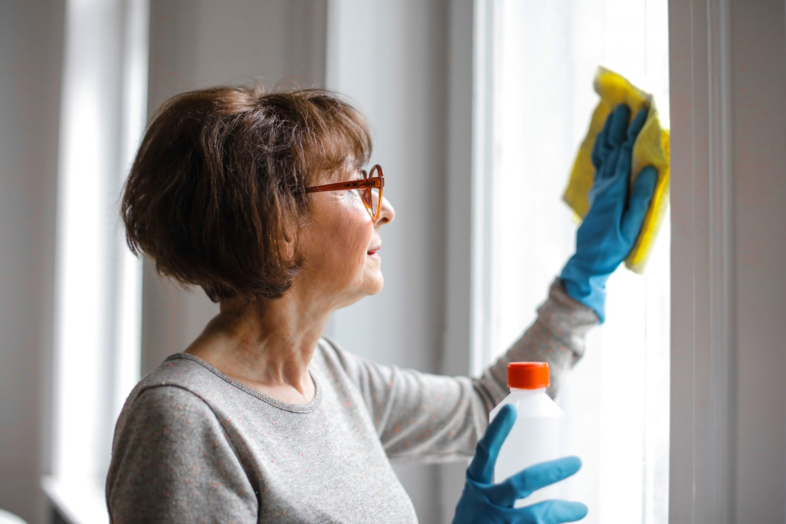 woman spring cleaning by cleaning her windows