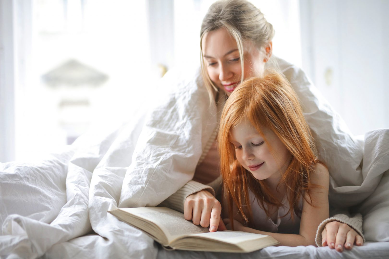 mother keeping her kids busy by reading a book to her daughter
