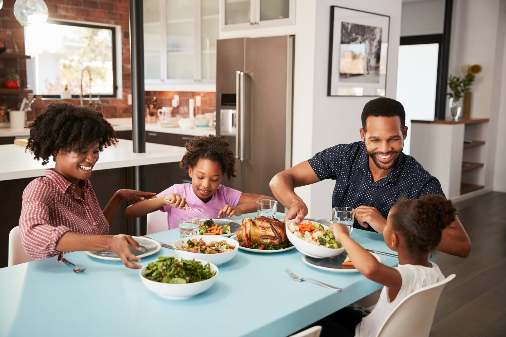 family of four eating dinner together while practicing social distancing