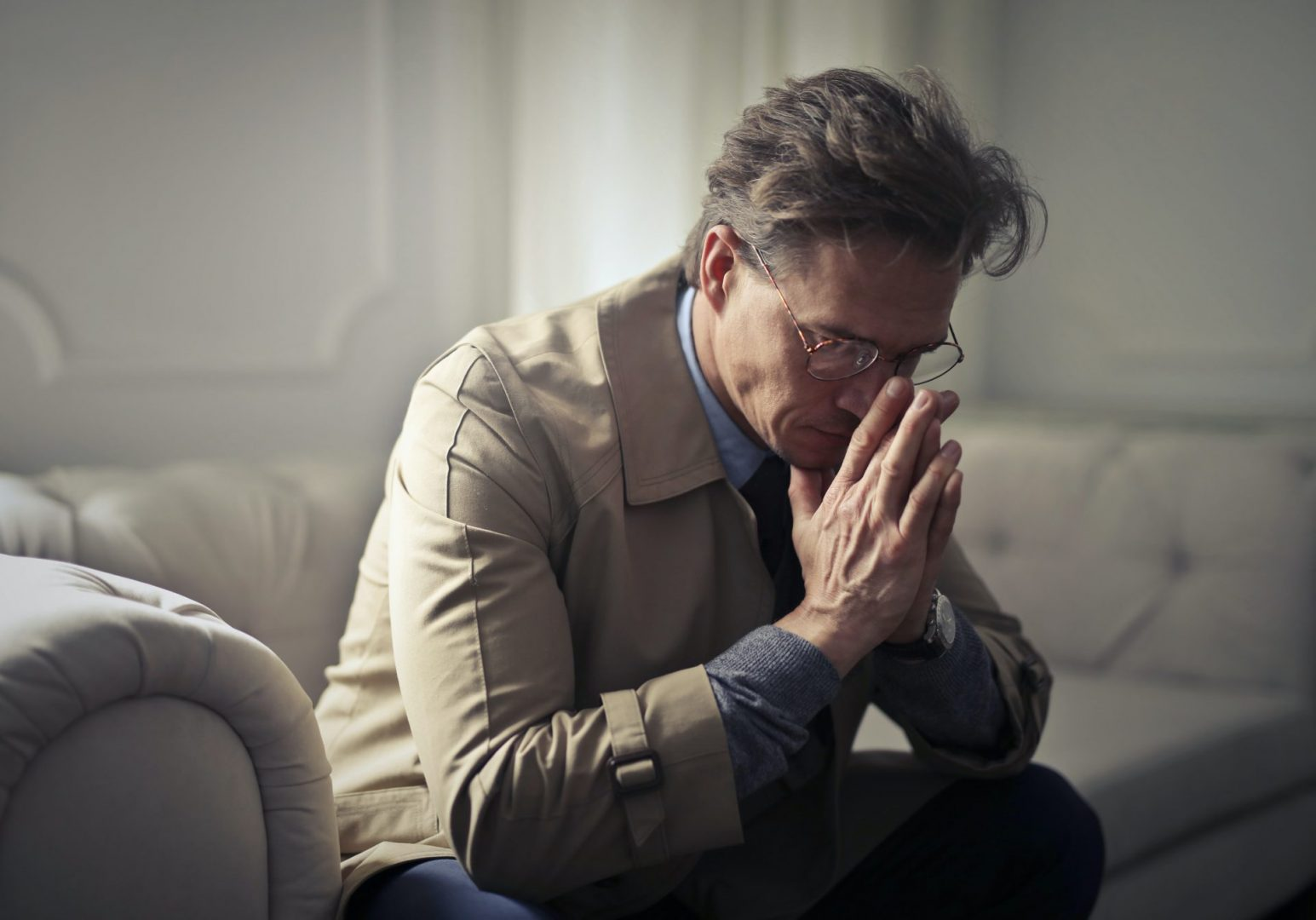 sad man sitting on the couch - National Prevention Week