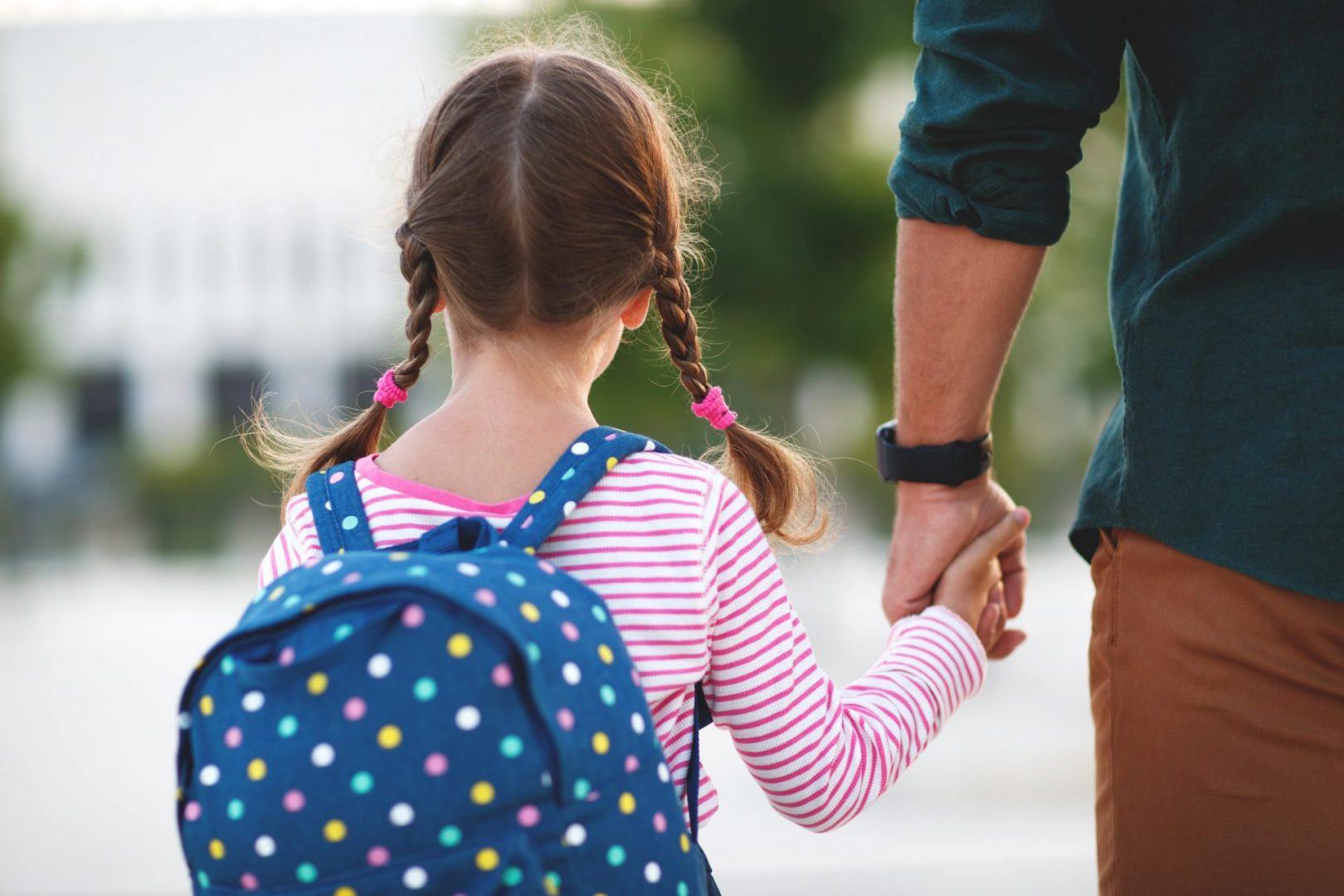 parent holding hand of little girl on the first day of school