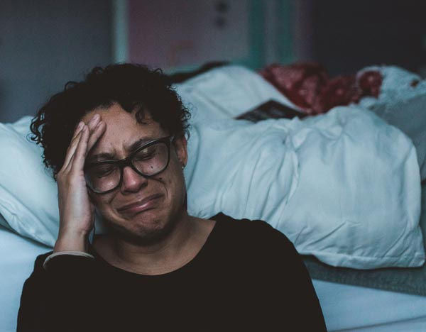 woman in grief crying next to bed