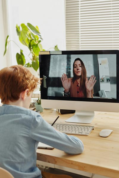 boy video chatting with woman for school