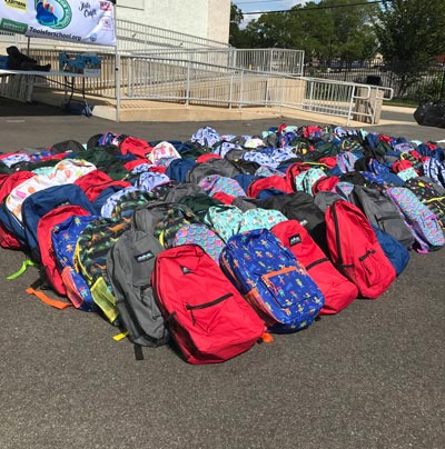 backpacks in parking lot for tools for schools