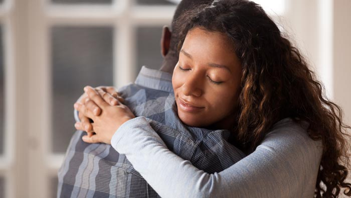 young woman hugging comforting loved one in recovery