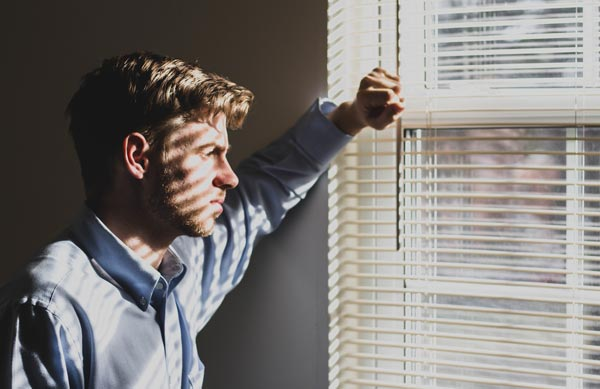 man looking out window mental illness awareness