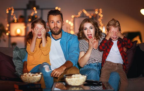 family sitting on couch watching scary halloween movies eating popcorn
