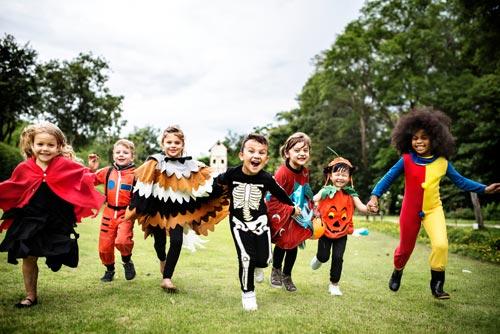 children running with halloween costumes