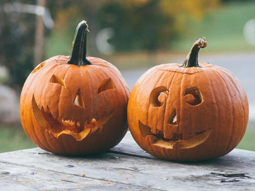 pumpkin carving two jack-o-lanterns on picnic table