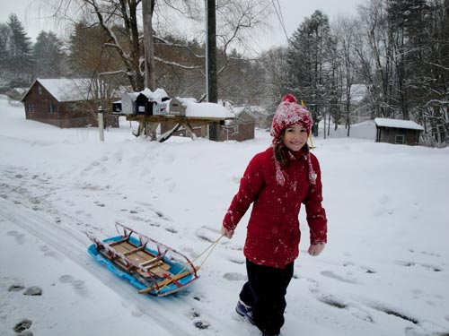 young girl pulling a sled in the winter
