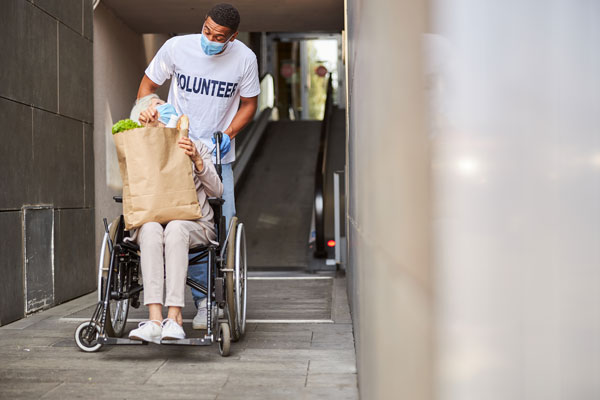 random acts of kindness day young volunteer helping older man in wheelchair with groceries