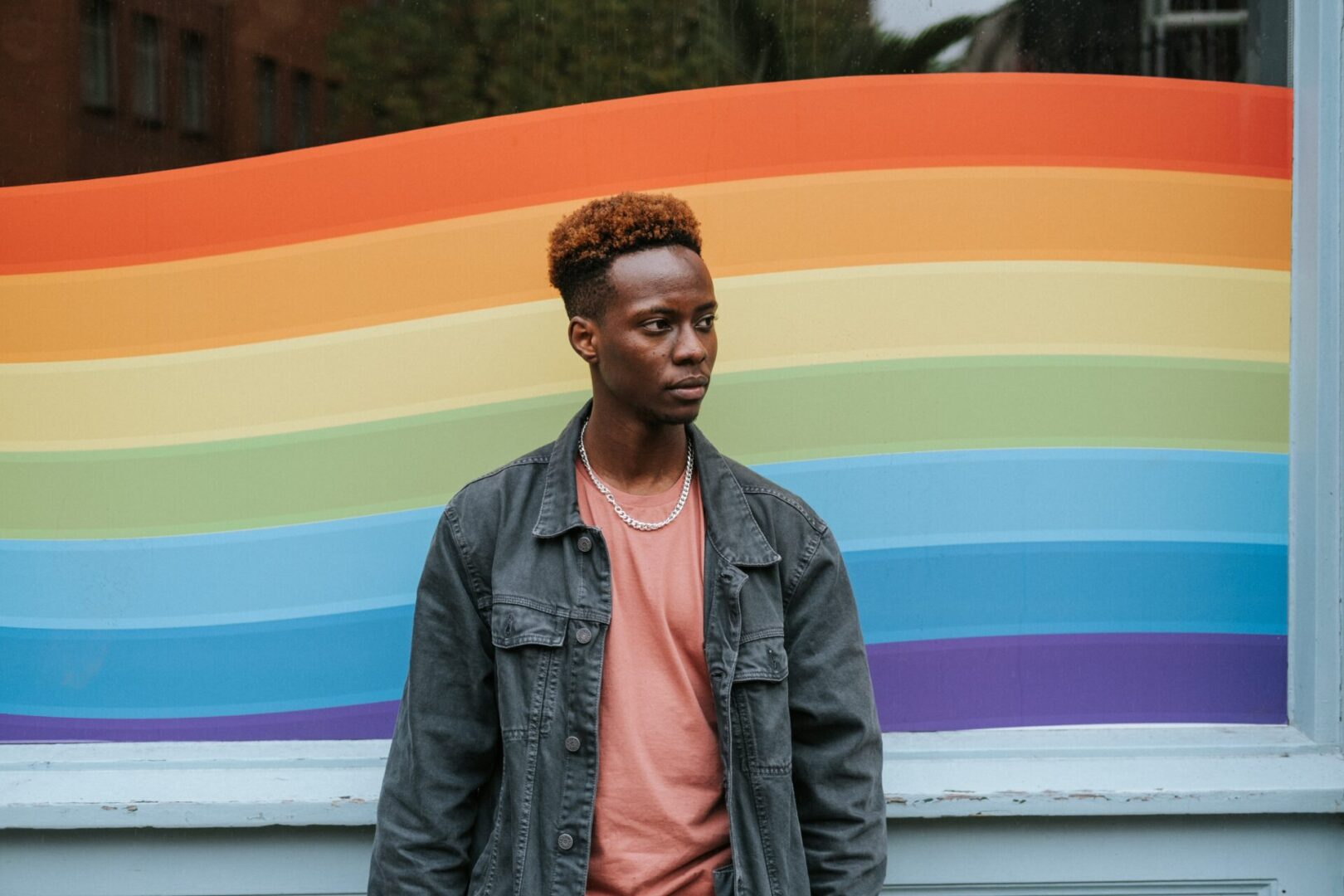 black young adult standing in front of rainbow background