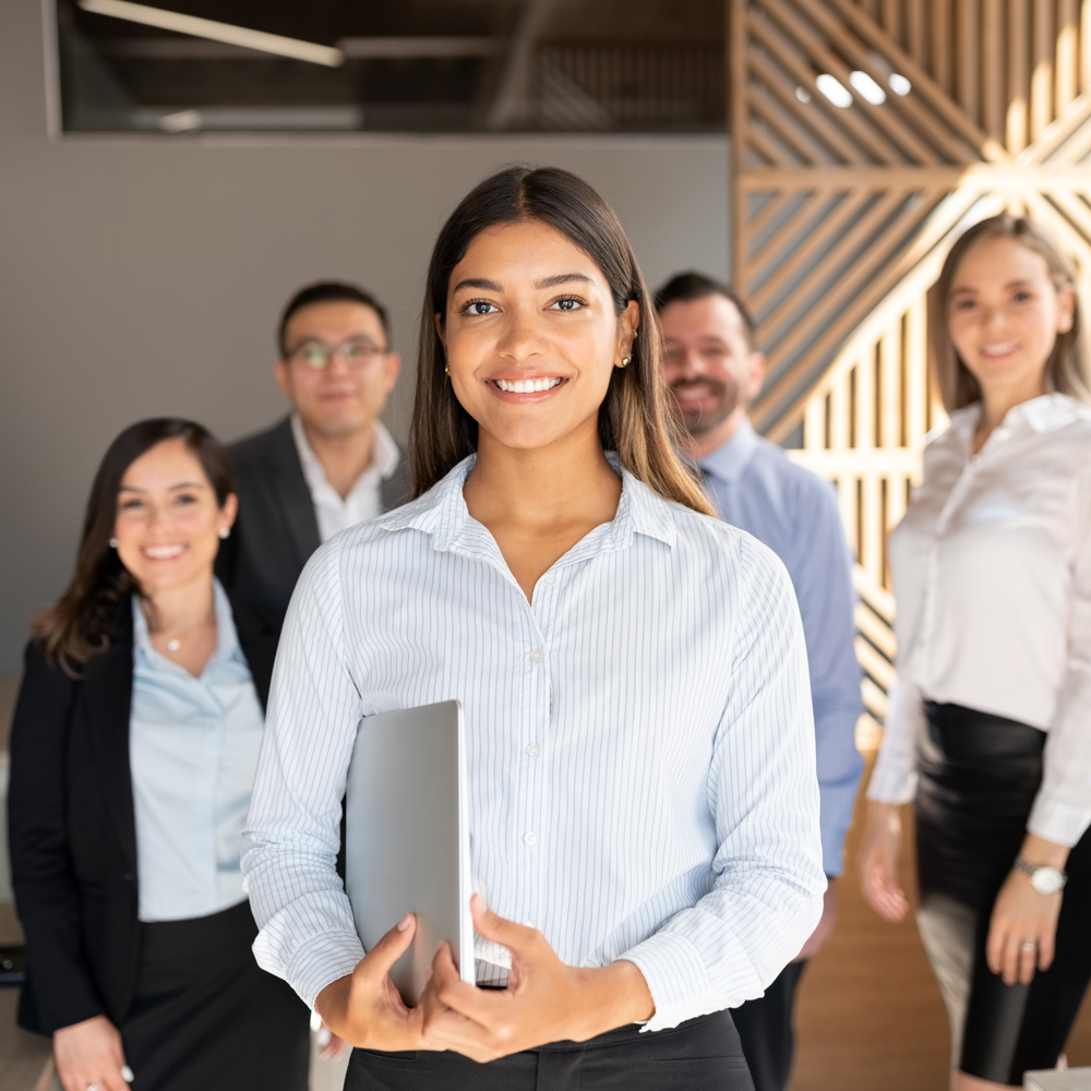 Confident hispanic businesswoman standing in office with colleagues in background.